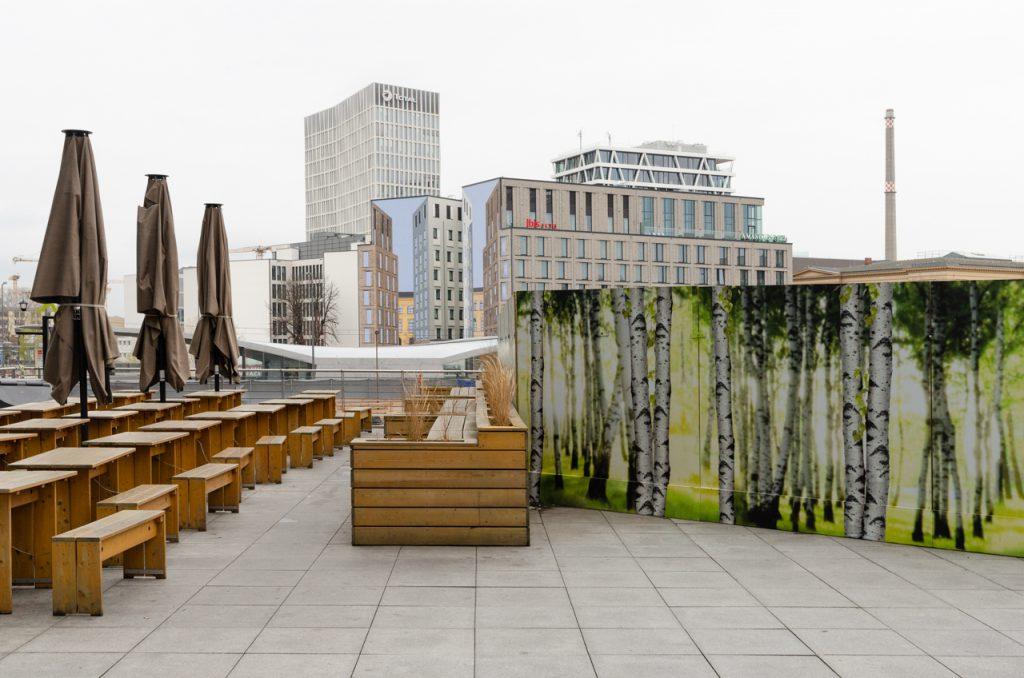 Hauptbahnhof Berlin. Blick von der Terrasse des Bahnhofsgebäudes Richtung Norden. Dort steht ein Hotelneubau, auf dessen Brandwand eine Fassade aufgemalt wurde. Auf der Terrasse befindet sich ein Bauzaun, der großflächig mit einer Birkenwaldabbildung verziert wurde.